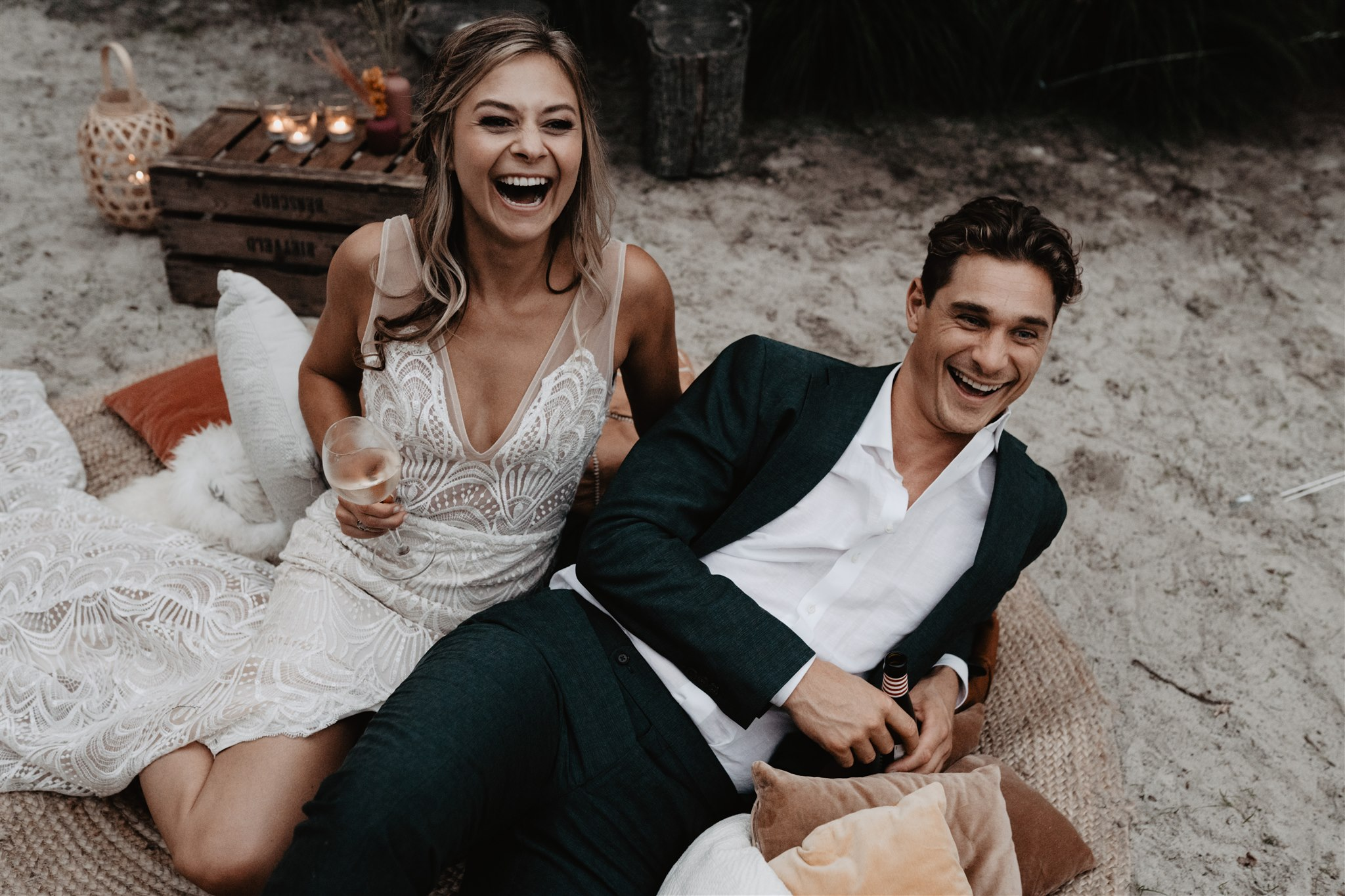 Bride and groom laughing laying barefoot on the sand